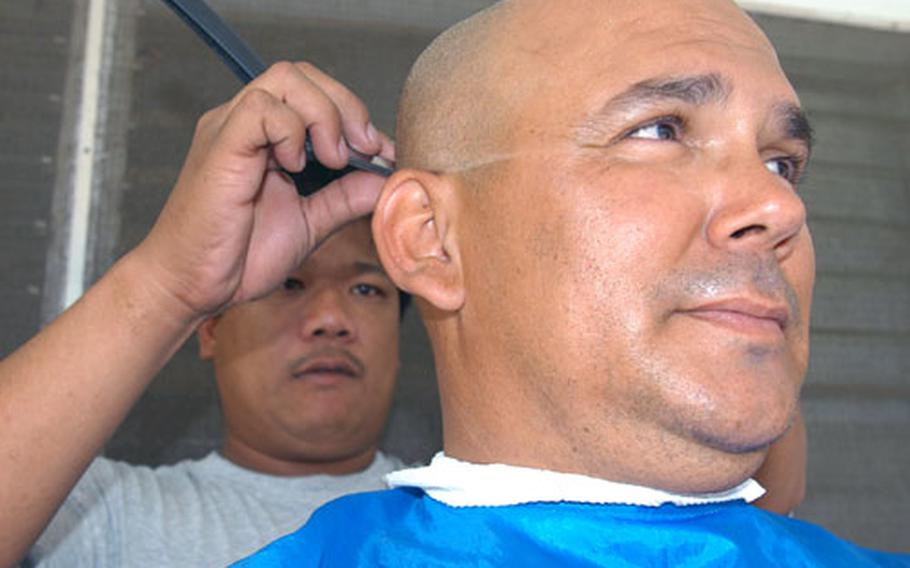 Spc. Elven Escobar, a member of the 1-185 Armor headquarters from San Bernardino, Calif., gets a haircut from a local barber.