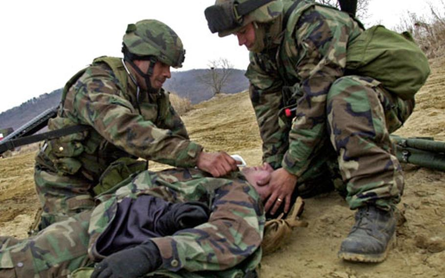 Staff Sgt. Duran Wilson, left, and Sgt. Todd Vance treat a simulated casualty during a field medical scenario at Warrior Base, South Korea, on Tuesday.