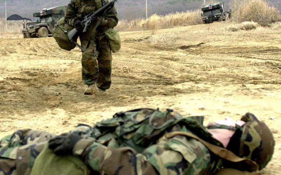 """Staff Sgt. Duran Wilson runs toward """"wounded"""" soldier Spc. Erik Hennlich during the field medical exercise."""