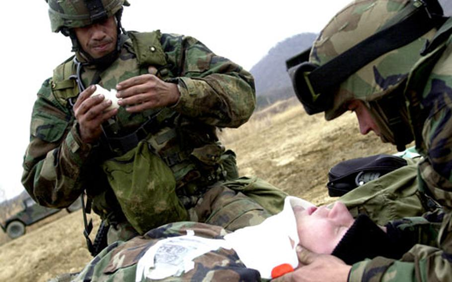 Staff Sgt. Duran Wilson and Sgt. Todd Vance treat a simulated casualty. Soldiers practiced setting up security while tending to the wounded under several attack scenarios.