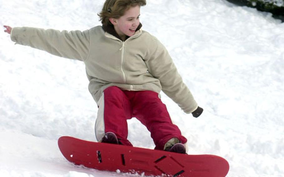 Neely O'Grady, 8, works the extreme edge of her snowboard on a slope below the conference center at H.D. Smith Barracks in Baumholder, Germany. The base got about 8 inches of snow overnight Wednesday.