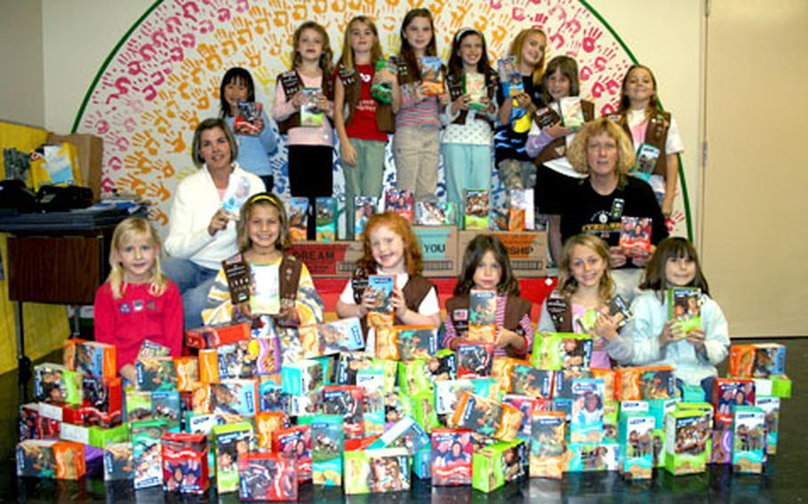 The girls of Brownie Troop 404 on Camp Foster pose with the more than 150 boxes of cookies they sent to servicemembers in Iraq and Afghanistan. The photo was included with the cookie packages and the girls have been receiving e-mails thanking them for their donations.