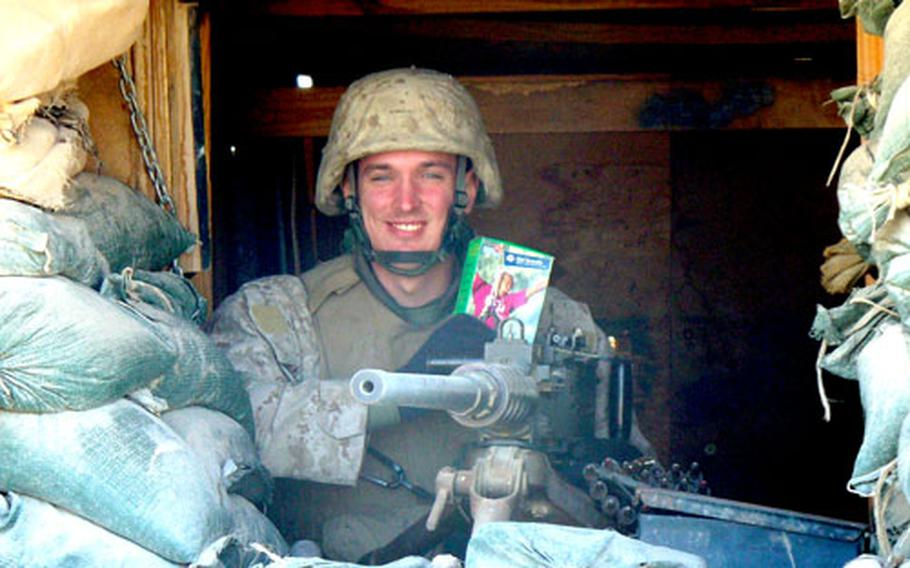 An unidentified Marine smiles as he holds a box of Thin Mints Girl Scouts cookies at his post in Fallujah, Iraq.