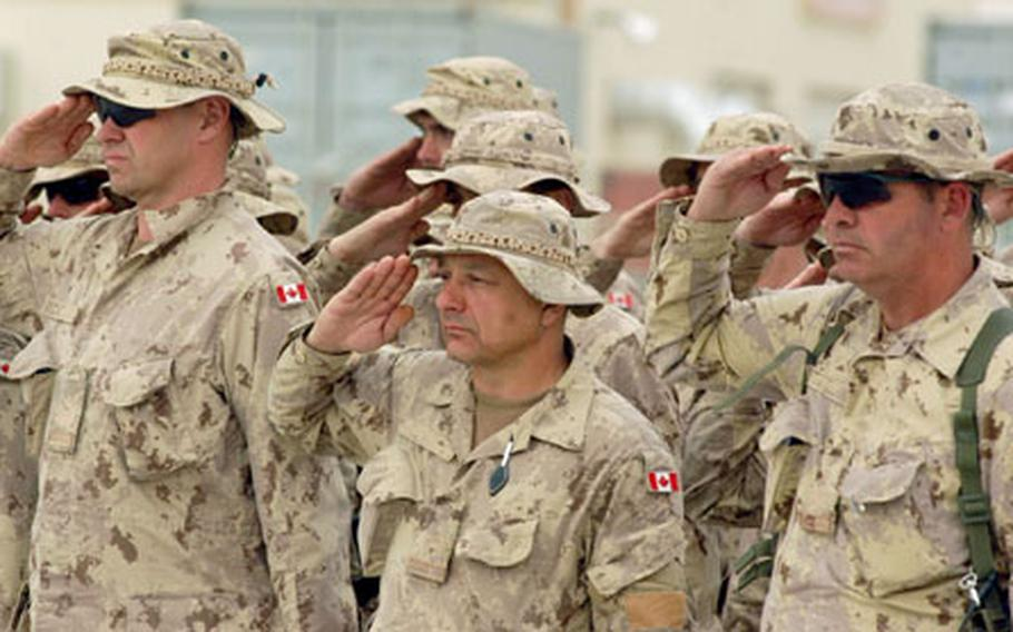 Canadian soldiers salute a fallen member of the 2nd Battalion, Princess Patricia's Canadian Light Infantry during a ramp ceremony Friday at Kandahar Airfield, Afghanistan. Cpl. Paul Davis, 28, was killed in a vehicle crash on Thursday.