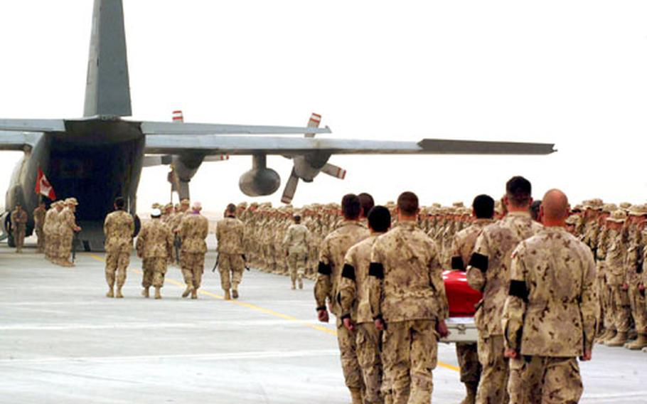 Canadian soldiers carry the coffin of Cpl. Paul Davis toward a C-130 Hercules cargo plane Friday during a ramp ceremony at Kandahar Airfield, Afghanistan.