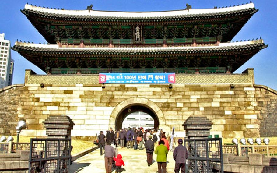 South Koreans flock through Namdaemun Gate for the first time in 99 years on Friday. The central passage through the gate was closed during the Japanese colonial period when gate walls were knocked down to make room for railroads and buildings.