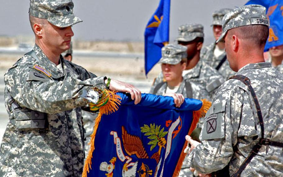 Lt. Col. Mark Patterson, left, and Command Sgt. Maj. Thomas Gordon unfurl the colors of the 2nd Battalion (Assault), 10th Aviation Regiment during a transfer of authority ceremony Saturday at Kandahar Airfield, Afghanistan.