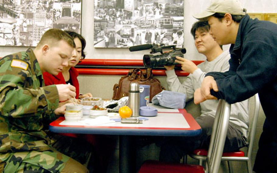 Army Sgt. Christopher Largent and his wife Yu-sung have lunch at the Camp Carroll, South Korea, food court while a video crew films them for an upcoming TV program on South Korea's KBS2 station.