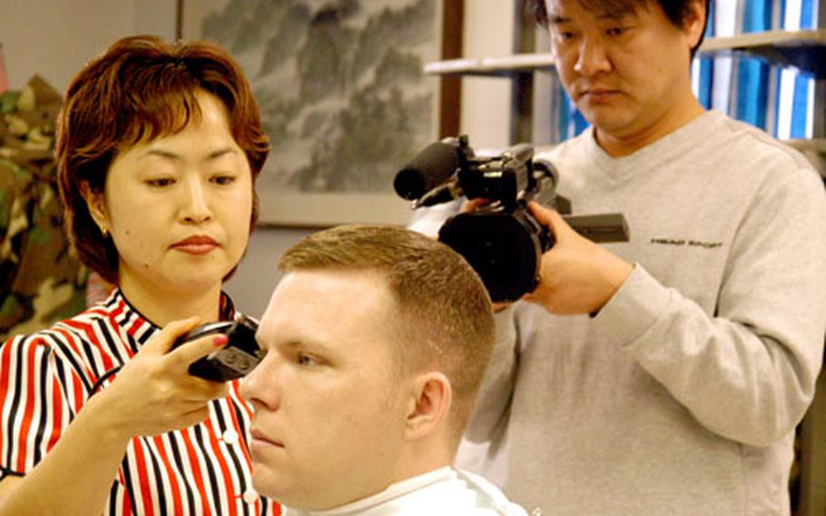 """Army Sgt. Christopher Largent gets a haircut while a video cameraman films him for an upcoming program on South Korea's KBS2 station. The station will air a set of segments about Largent and his South Korean wife during its 8:50 p.m. broadcasts of March 6-10 show called """"In Gan Geuk Jang."""""""