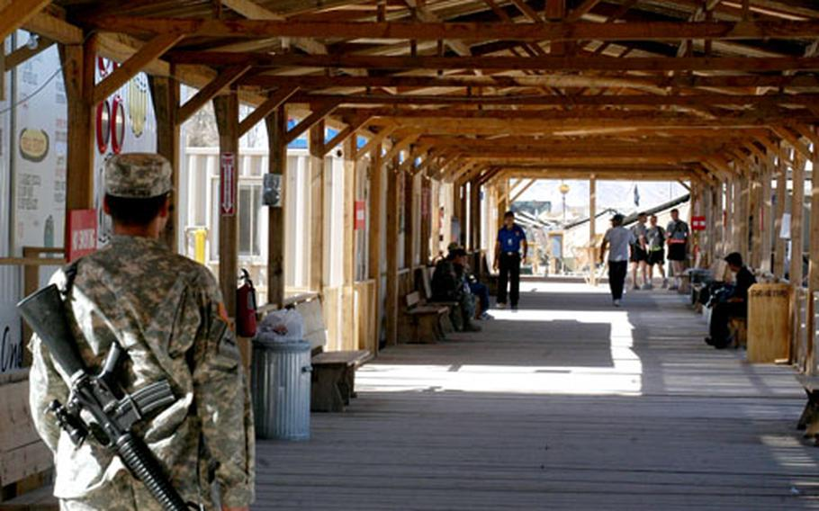 A wooden boardwalk lies at the heart of Kandahar Airfield in Afghanistan. Trailers featuring restaurants and shops line the exterior of the boardwalk, with a large open space in the interior that might one day sport athletic fields.