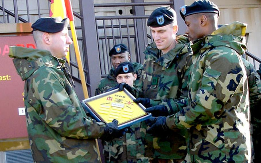 Col. John Rossi, left, presents a plaque to Capt. Brian Moore, center, and 1st Sgt. Michael Hudson, both of Headquarters and Headquarters Battery, at Osan Air Base, South Korea, on Friday.
