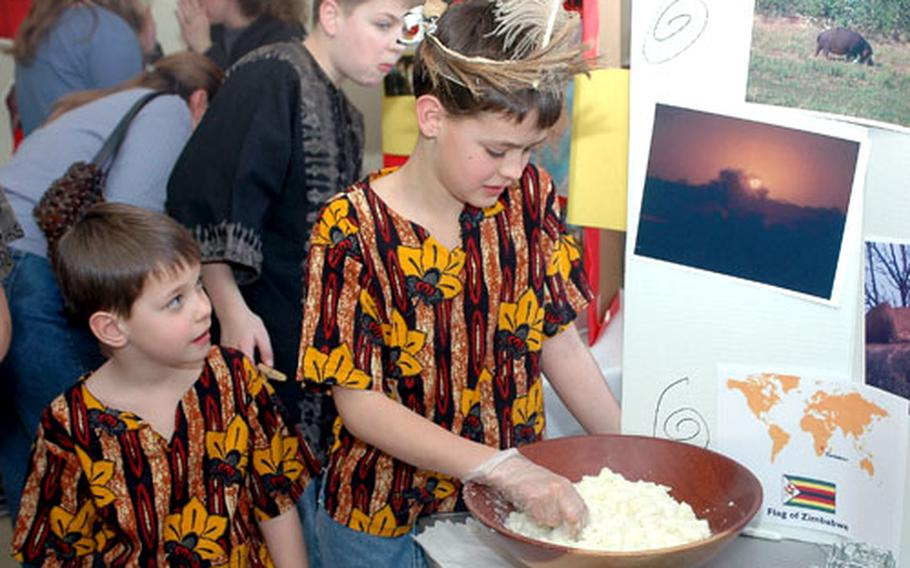 Wyatt and Gideon Castle tumble dough to make a traditional Zimbabwean meal Feb. 24 at the South Post Chapel.