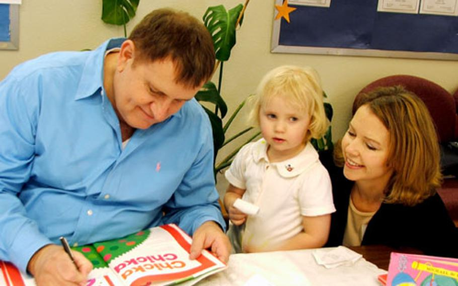 """Michael Sampson signs a copy of """"Chicka, Chicka 1 ... 2 ... 3"""" for Rebeka Wuerch, 3, and her mom, Miryam. The book is one of the best-sellers Sampson wrote with his late writing partner, Bill Martin Jr."""