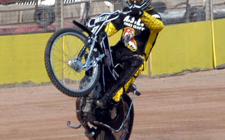 A member of the Fen Tigers racing team shows off by popping a wheelie with his 500cc racing bike while on the Mildenhall Speedway track during a recent practice run.