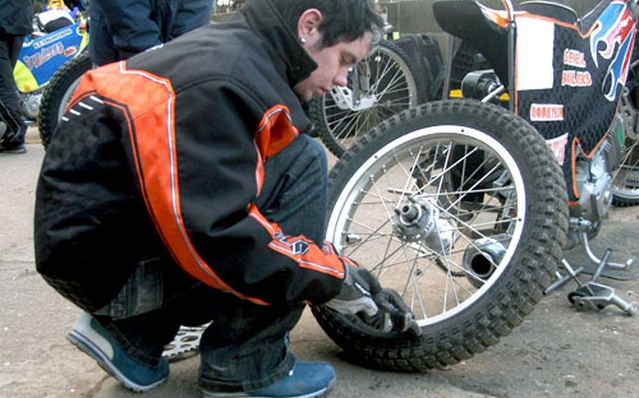 Rob Smith, 18, changes a tire on a 500cc racing bike for a friend at the Mildenhall Speedway track.