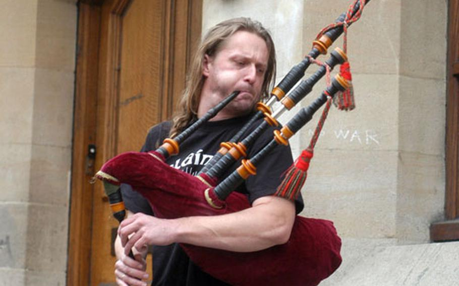 Street performer Heath Richardson plays the bagpipes for anyone who cares to listen along Cornmarket Street, a popular shopping area in Oxford.