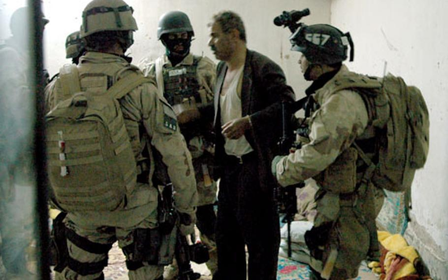U.S. and Iraqi special operations personnel help a kidnapping victim to his feet Monday. The hostage was found shackled to a steel bed in an apartment building east of Taji.
