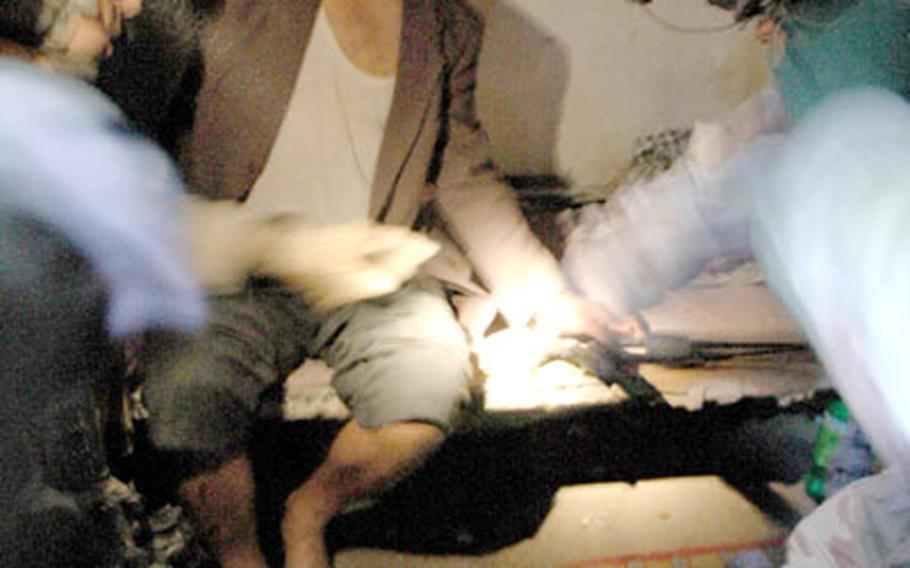 Soldiers cut the handcuffs from the hostage.