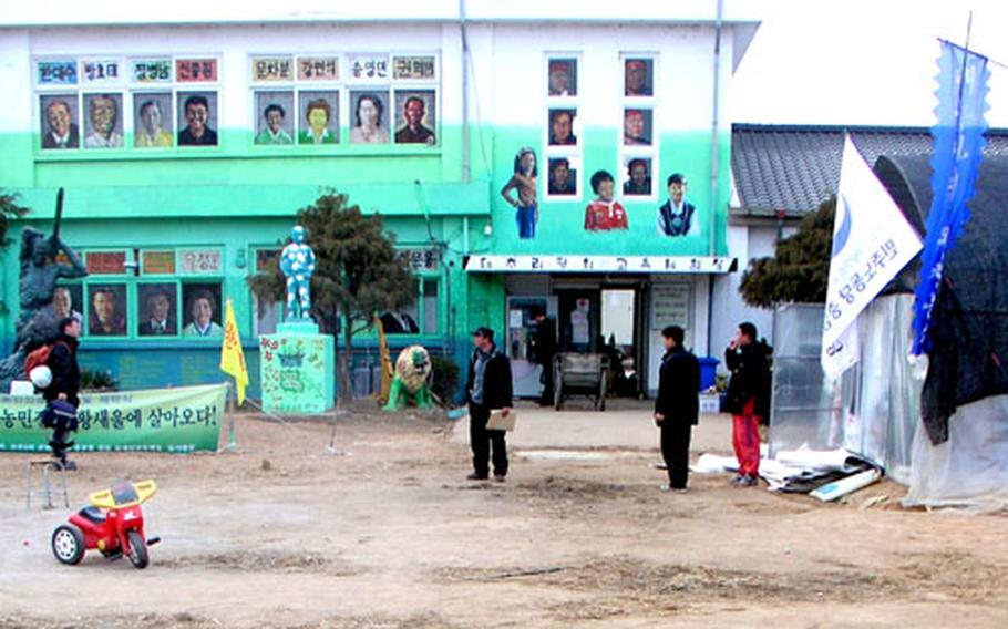 Several men mill about inside the barricaded grounds of the Daechu-ri Elementary School on Tuesday.