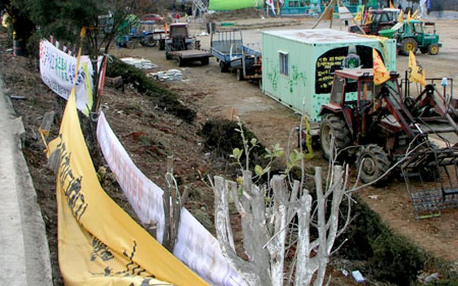 A view from a street just above the grounds of the Daechu-ri Elementary School shows vehicles and heavy equipment lined up in a barricade.