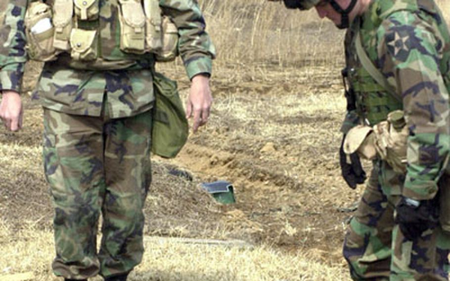 Soldiers examine damage to a dummy by ammunition designed for closer attacks.