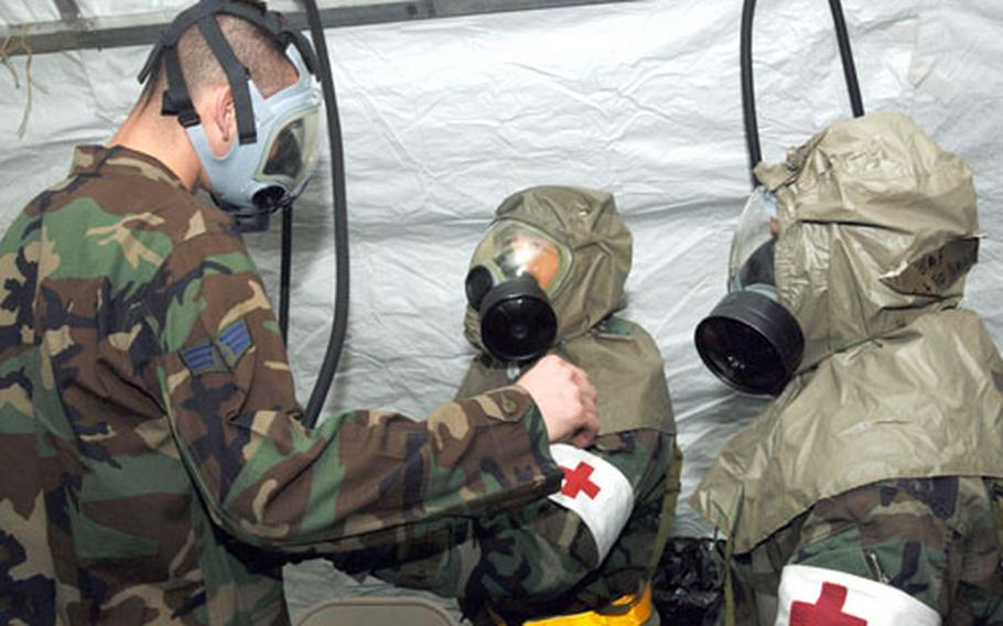 """""""Contaminated"""" patients pass through a decontamination tent connected to the 374th Medical Group's emergency room entrance before admission to the hospital during an Operational Readiness Exercise at Yokota Air Base, Japan, in January. Since hospital staff members, including physicians and technicians, have specific roles during exercises, Yokota's primary care clinics commonly defer routine appointments until the end of a basewide drill or inspection. But medical officials say essential services are never shut down."""