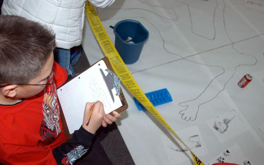 Zach Nichlos jots down notes during the first day of the inaugural Mystery Festival held recently at Cummings Elementary School at Misawa Air Base, Japan. Students in grades four, five and six used science to try and solve a scripted murder mystery, complete with clues such as footprints, fake blood and a body outline.