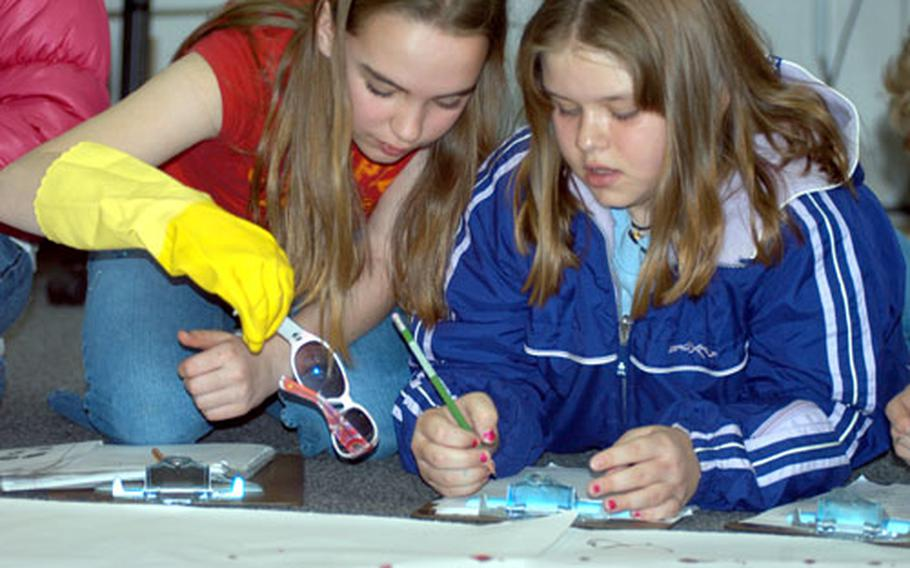 """Melissa LaChance, left, and Lauren Day examine a pair of sunglasses left at the """"crime scene"""" during Cummings Elementary School's Mystery Festival."""