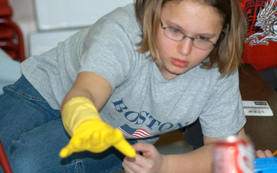 """Jacqueline Armour reaches for a clue at the """"crime scene."""""""