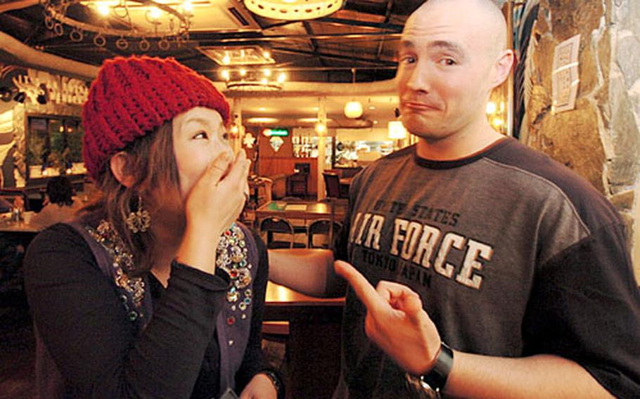 Airman 1st Class Brian Anderson makes waitress Youko Takeshita laugh in his off time from working at Yokota Air Base, Japan. Anderson, a comedian for more than two years, has a show at the Maple Leaf in Shibuya on March 26.