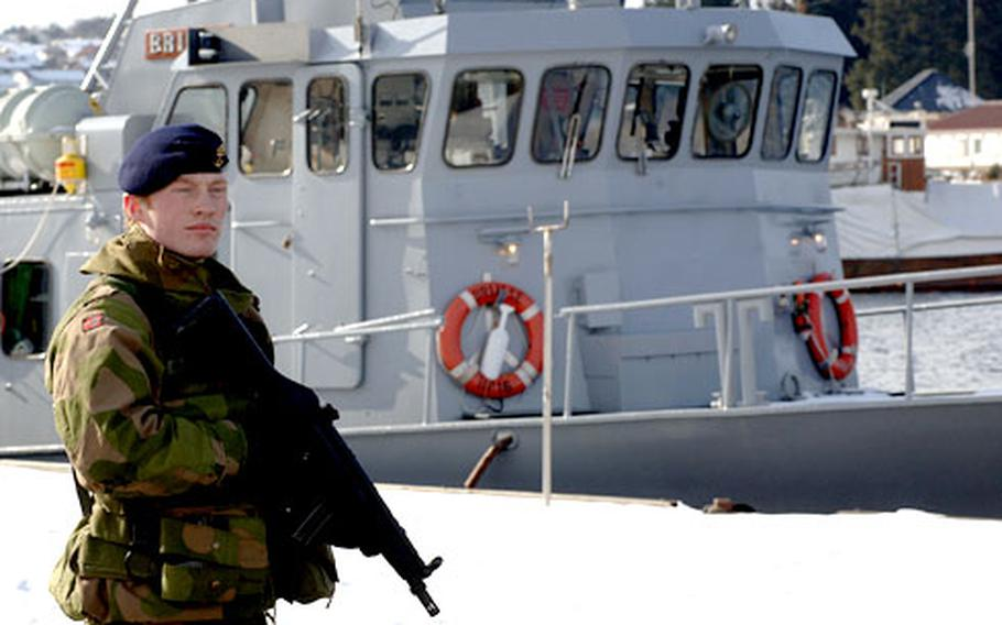 A member of the Norwegian security forces patrols the waterfront at NATO's Joint Warfare Center in Stavanger, Norway.