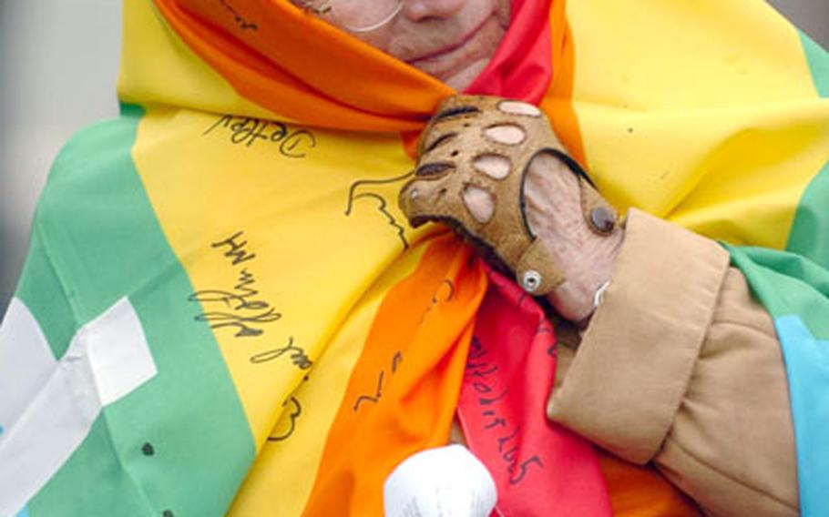 A elderly women wrapped in a peace flag sings a hymn outside Ramstein Air Base, Germany, on Saturday. Approximately 20 protesters gathered to voice opposition to the U.S.'s involvement in Iraq.
