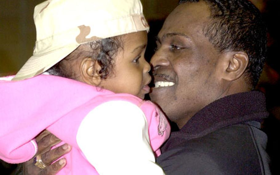 Master Sgt. Curtis Clinton holds his 2-year-old daughter, Ramyrah.