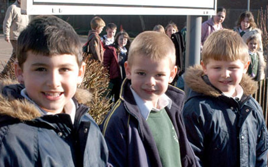 American brothers Trevor Hill, 5, left, and Devon Hill, 7, right, stand with their English schoolmate Matthew Woodward, 7, outside Great Hockham Primary School near Thetford. Devon and Trevor's parents are Tech. Sgt. David and Maria Hill.