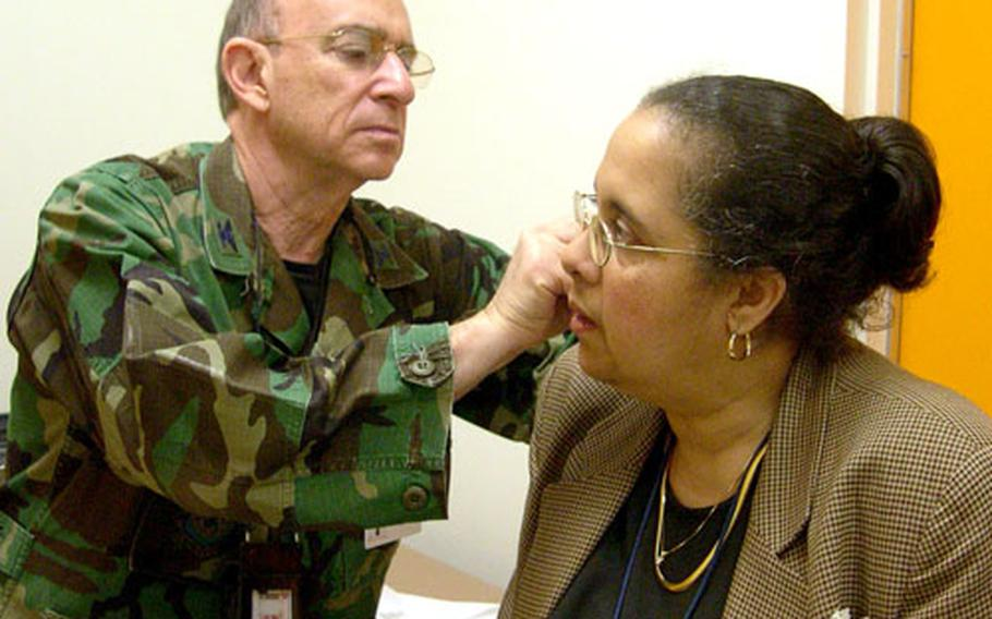 file - Joyce Brentley winces as Air Force Col. Richard Niemtzow inserts a tiny needle into her earlobe during an acupuncture session at Walter Reed Army Medical Center.