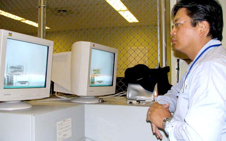 Japanese Customs inspector Masaichi Yamauchi checks the X-ray pictures of mail being processed.