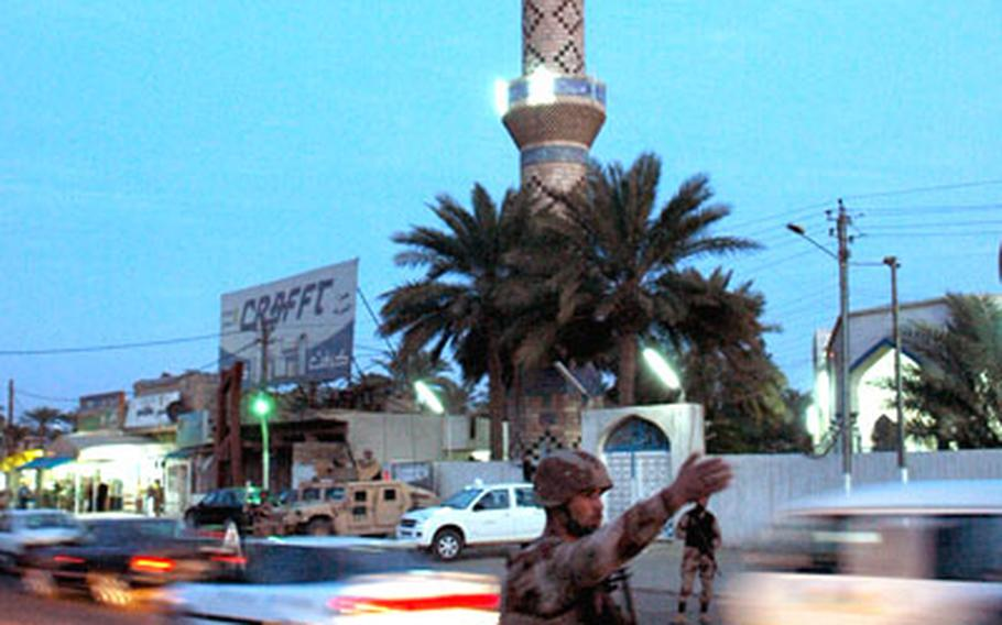 An Iraqi army soldier holds a security perimeter around a prominent Sunni mosque in a Baghdad neighborhood.