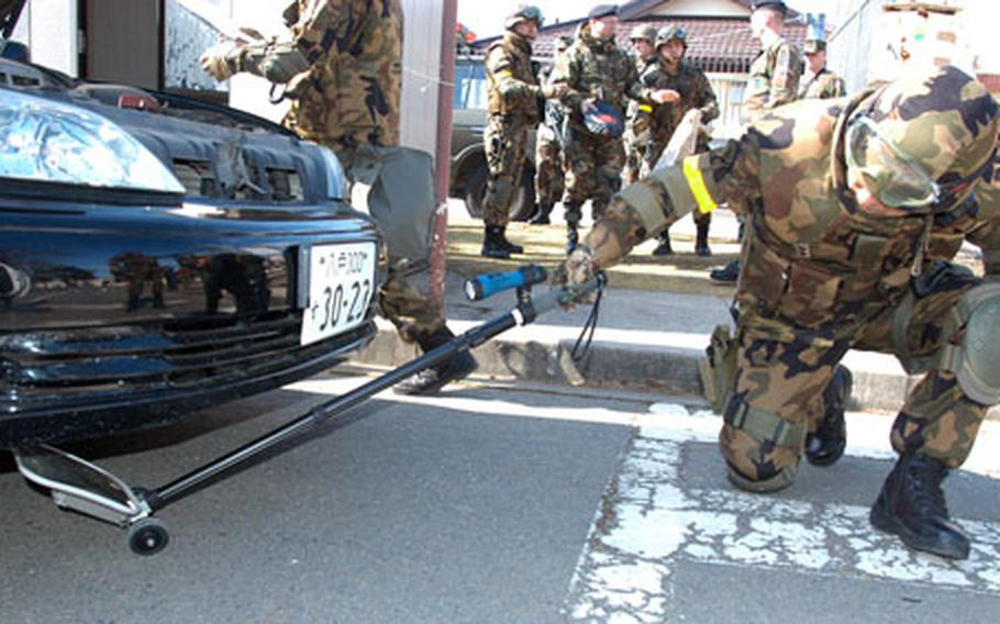 A Japan Air Self-Defense airman inspects the underbelly of a car during a random vehicle check Wednesday morning at Misawa.