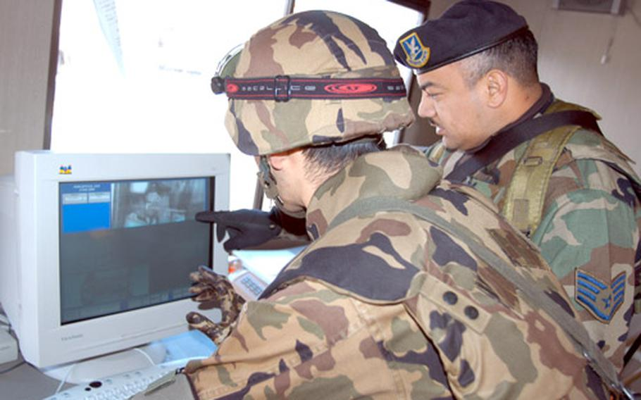 Staff Sgt. Antonio Gomez, right, of the 35th Security Forces Squadron, and Senior Airman Arima Norikazu, 3rd Air Wing, examine a digital photo of a vehicle's undercarriage.