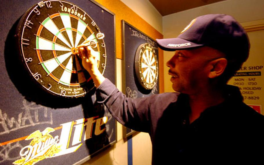 Ron Harmon, a civilian contractor with the 374th Communications Squadron, throws darts Tuesday afternoon at the enlisted club on Yokota Air Base, Japan.