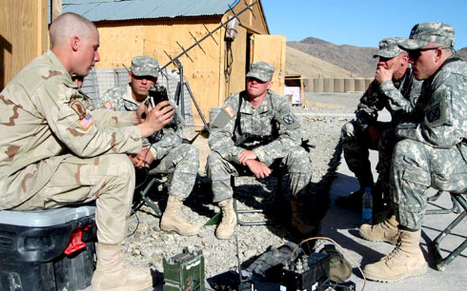 Spc. Jason Slomiak of 3rd Platoon, Company B, 2nd Battalion, 503rd Infantry Regiment, 173rd Airborne Brigade goes over communications equipment with soldiers of 1st Platoon, Company A, 2nd Brigade, 4th Infantry Regiment, 4th Brigade, 10th Mountain Division at Forward Operating Base Arghandab, Afghanistan.