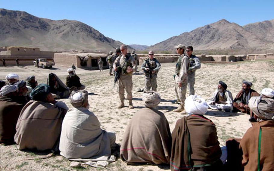 Second Lt. Ian Dietz, left, of 3rd Platoon, Company B, 2nd Battalion, 503rd Infantry Regiment, 173rd Airborne Brigade, and 1st Lt. Ryan Edwards, 1st Platoon, Company A, 2nd Brigade, 4th Infantry Regiment, 4th Brigade, 10th Mountain Division, center, talk to village elders during an orientation tour of the villages near Forward Operating Base Arghandab in Afghanistan. The 10th Mountain soldiers are taking over the FOB from the soldiers of the 173rd.