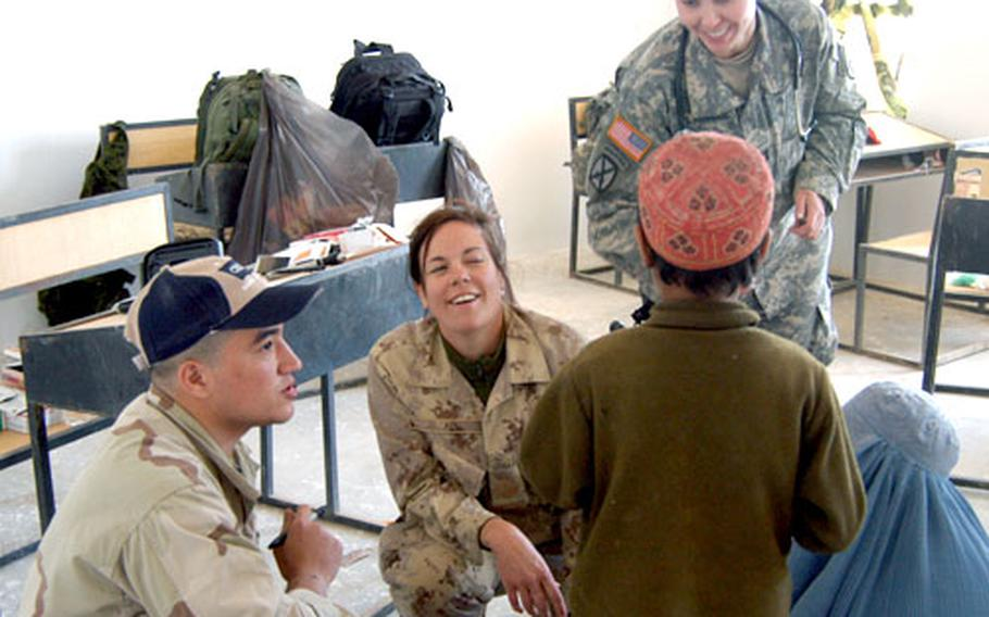 With the help of a translator, left, Canadian Army medic Sgt. Susan Paul, center, gives an Afghan boy some medicine and Capt. Darby Sivernail of the 10th Mountain Division, right, gives him some candy. The boy and his mother were visiting the doctors during a village medical outreach mission held by coalition forces.