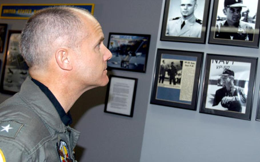 /Rear Adm. Brian Prindle, commander of Patrol and Reconnaissance Group in Norfolk, Va., views photographs and news clippings of his late father.