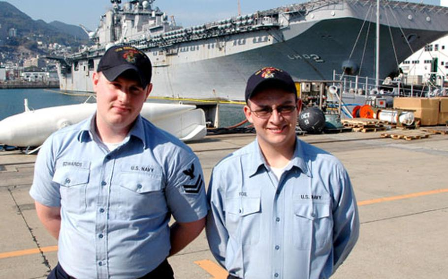 Petty Officer 2nd Class Timothy Edwards, left, and Petty Officer 3rd Class Timothy Vigil, USS Essex shipmates, stand at the India Basin pier at Sasebo Naval Base on Friday. The two helped several Japanese neighbors to safety and tried to rescue two others who died in a house fire in their off-base neighborhood Thursday night.