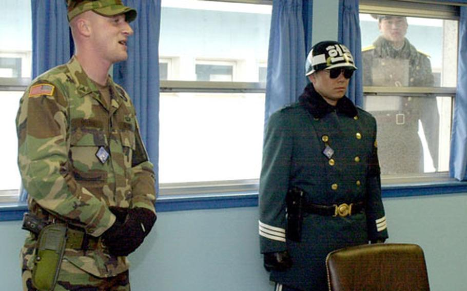 A curious North Korean soldier, right background, peeks in on a distinguished visitor tour given by security escort Sgt. John Dotson, left, at the Joint Security Area recently.