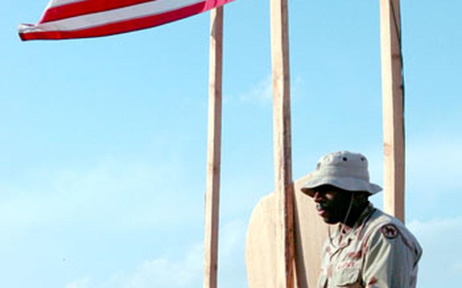 A soldier from the 391st Engineering Battalion sits in the shadow of the flag, which was at half-staff this week at Jalalabad Airfield following the deaths of four soldiers from the Army Reserve unit.