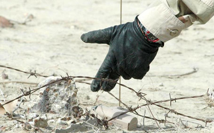 A bomb disposal expert points to an illumination grenade found in the sand in southern Iraq.