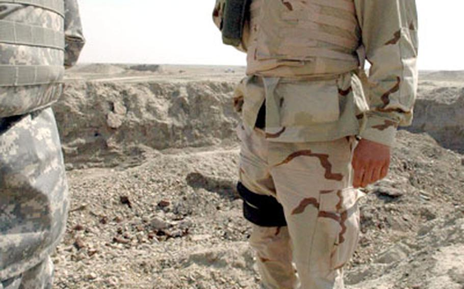 Capt. Draze Guto prepares to destroy munitions collected during a search of the desert on the outskirts of Nasiriyah.