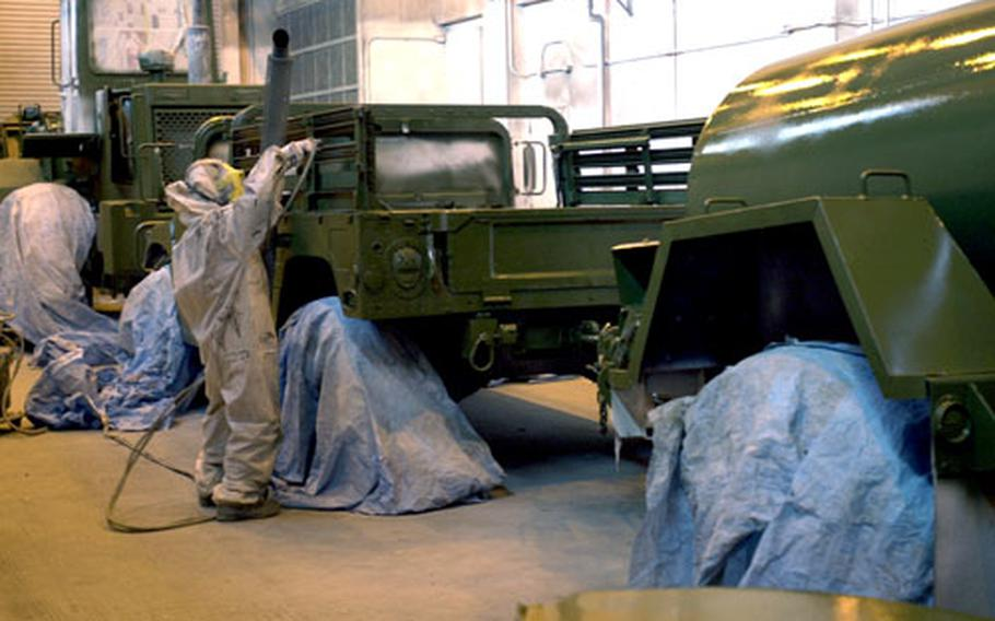 A worker at the Corrosion Rehabilitation Facility on Camp Kinser applies a base coat of green paint to a Humvee and portable water tank. The facility takes rust off of gear, repairs it and puts on new paint.